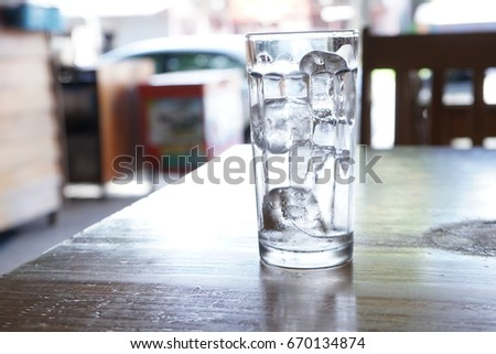 Crystal glass with ice cubes on the table. #670134874