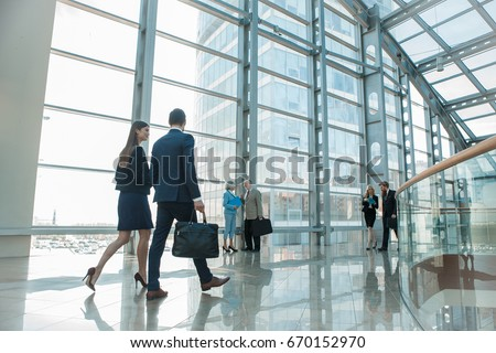 Business people walking in modern glass office building Royalty-Free Stock Photo #670152970