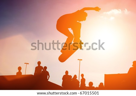 Jumping skateboarder silhouette over sunset sky background #67015501