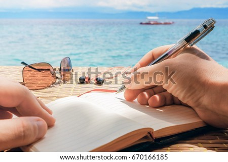 caucasian man is writing some idea, message or letter in his notepad by pen in his right hand while he sitting on the beach of tropical sea with boat at sunny day