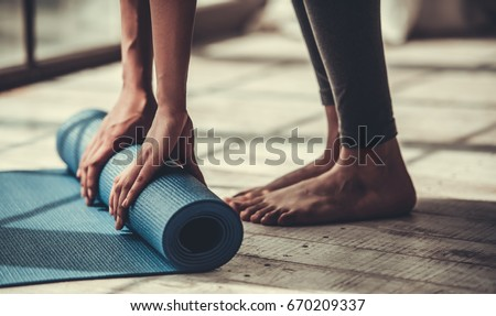 Cropped image of Afro American rolling yoga mat Royalty-Free Stock Photo #670209337