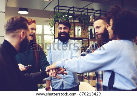 Team of creative graphic designers celebrating finishing work on successful project high-fiving in good mood standing in modern coworking office for conference feeling happy about improvement  #670213429