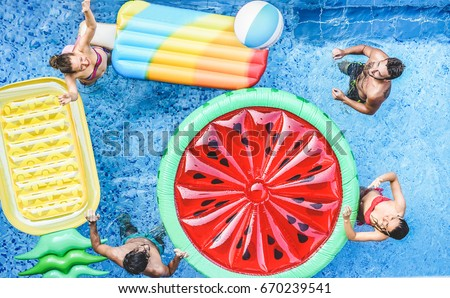 Happy friends playing with ball inside swimming pool - Young people having fun on summer holidays vacation - Travel,holidays,youth,friendship and tropical concept - Seasonal color tones filter #670239541