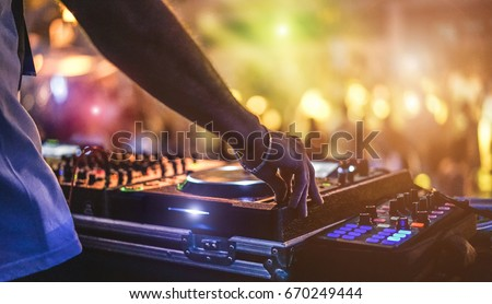 Dj mixing outdoor at beach party festival with crowd of people in background - Summer nightlife view of disco club outside - Soft focus on hand - Fun ,youth,entertainment and fest concept Royalty-Free Stock Photo #670249444