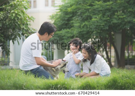 Happy Asian family playing with siberian husky dog in the garden #670429414