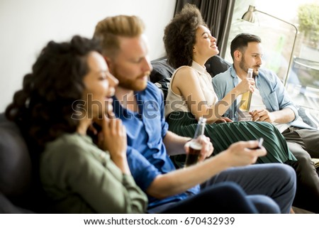 Group of friends watching TV , drinking cider and having fun in the room #670432939