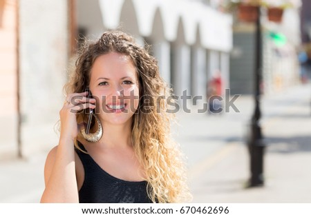 young woman talking on mobile phone on street in summer #670462696