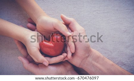 adult and child hands holding red heart, health care, love and family insurance concept, world heart day #670476097