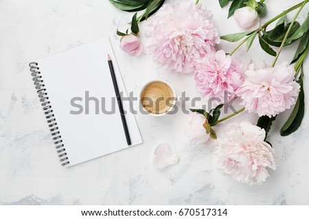 Morning coffee mug for breakfast, empty notebook, pencil and pink peony flowers on white stone table top view in flat lay style. Woman working desk. Royalty-Free Stock Photo #670517314
