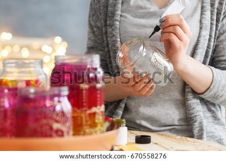 Young woman decorating DIY jars with paint Royalty-Free Stock Photo #670558276