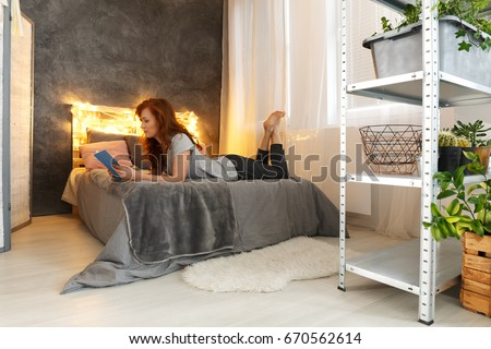 Woman reading book on elegant bed in stylish decorated apartment #670562614