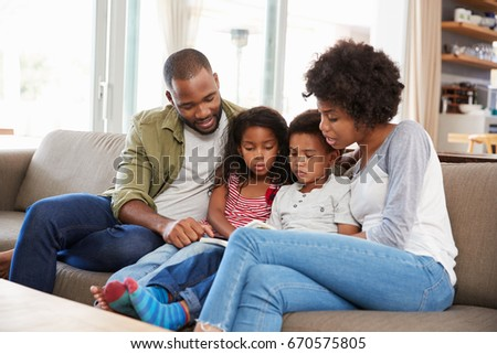 Family Sitting On Sofa In Lounge Reading Book Together #670575805