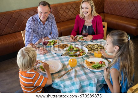 High angle view of happy family talking while dining at restauranrt #670589875