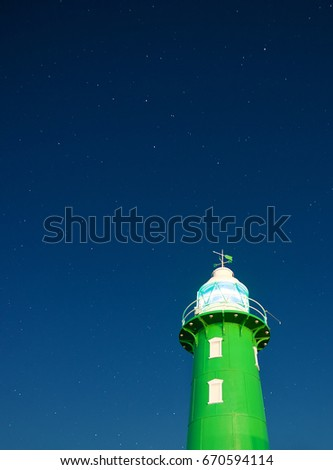 Green lighthouse at harbor with starry sky background #670594114