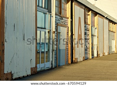 Old sheds at harbor in Western Australia. The photo was taken with early morning sun reflecting on the building. The harbor is reflected in the windows #670594129