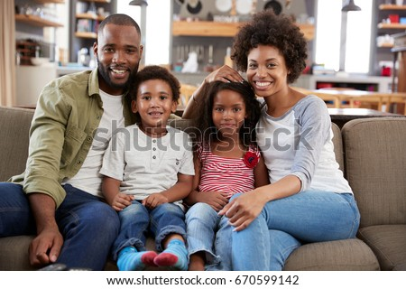 Portrait Of Happy Family Sitting On Sofa In Open Plan Lounge #670599142