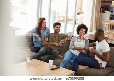 Couple Sitting On Sofa With Friends At Home Talking #670599208