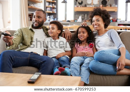 Family Sitting On Sofa In Open Plan Lounge Watching Television #670599253