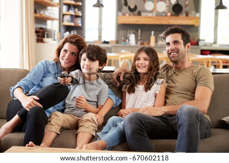 Family Sitting On Sofa In Open Plan Lounge Watching Television #670602118