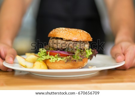 Waiter serves hamburger on a plate  #670656709