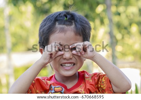Portrait of asian little boy smiling face looking with eyes contact to camera #670668595