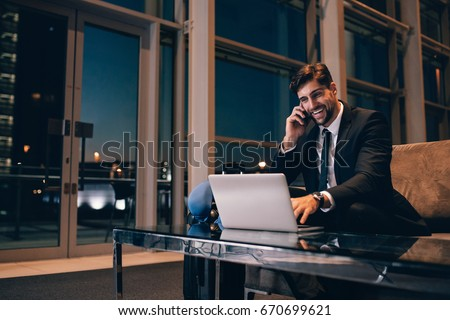 Smiling businessman with laptop talking on cellphone at the airport waiting lounge. Handsome man at waiting room in airport terminal. Royalty-Free Stock Photo #670699621