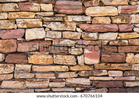 texture a closeup of a fragment of a stone wall or a part of a stone fence for a background #670766104