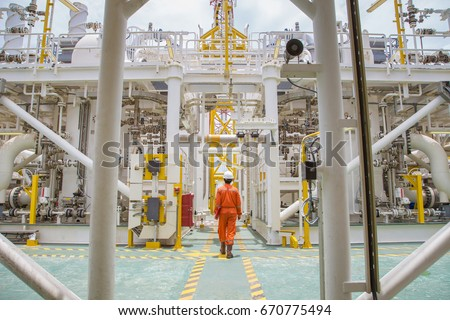 Technician walking through offshore oil and gas process for checking the condition of equipment on platform. #670775494