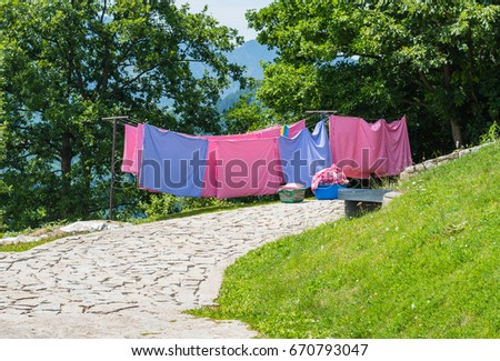 drying sheets on the line in the backyard, trees and mountains in the back #670793047