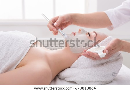 Face peeling mask, spa beauty treatment, skincare. Woman getting facial care by beautician at spa salon, side view, close-up #670810864