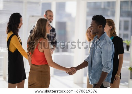 Happy colleagues shaking hands in office #670819576