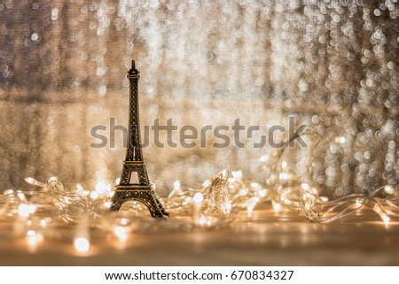 The Eiffel model rests on a wooden desk garland light has a background and has a blurry background.