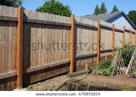 Yard fence backside with part on a retaining wall #670892854