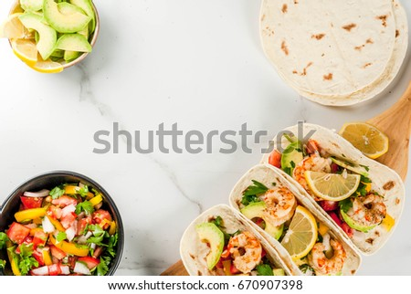Seafood. Mexican food. Tortilla tacos with traditional homemade salsa salad, parsley, fresh lemon, avocado and grilled shrimp pawns. On a white marble background. Top view copy space #670907398