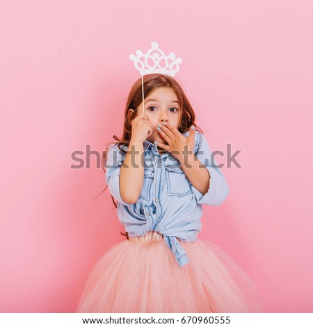 Cute beautiful carnival kid having fun isolated on pink background. Pretty little girl with long brunette hair, in tulle skirt, with white crown on head expressing wondering to camera #670960555