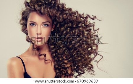 Brunette  girl with long  and   shiny curly  hair .  Beautiful  model woman  with wavy hairstyle Royalty-Free Stock Photo #670969639