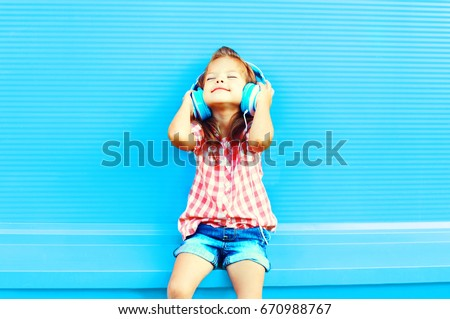 Happy little girl child listens to music in headphones on a colorful blue background #670988767