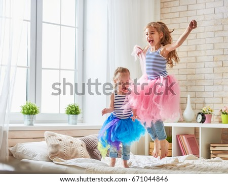 two cute children baby girls playing and having fun in the kids room. loving sisters jumping on the bed.