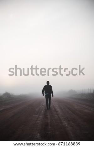 Man walking alone on misty road #671168839