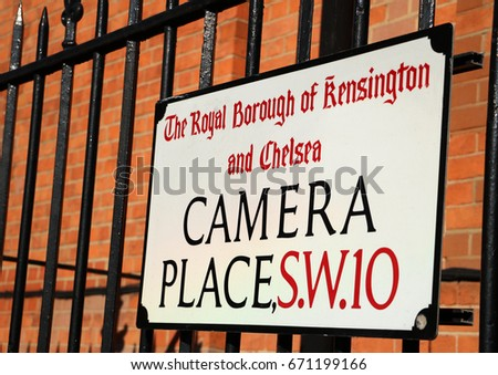 Camera Place: Colour photograph of street sign against red brick wall with black railings, in Chelsea, London. #671199166