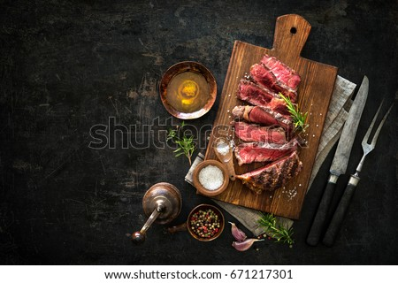 Sliced medium rare grilled beef ribeye steak on cutting board on dark background #671217301