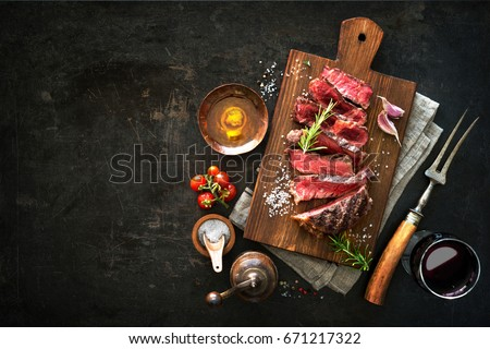 Sliced medium rare grilled beef ribeye steak on cutting board on dark background #671217322