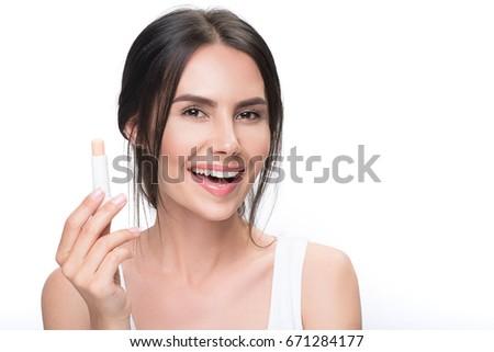 Happy girl applying chapstick on lips #671284177