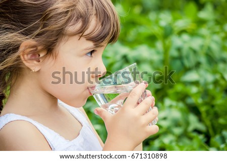 Child drinks water. Royalty-Free Stock Photo #671310898