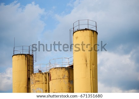 vivid yellow storage pipes of the abandoned factory against the blue sky #671351680
