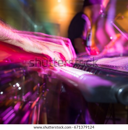 Musician plays keyboards in a rock band #671379124