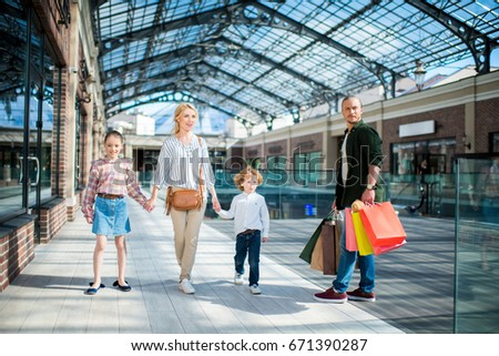 parents and little kids walking together in shopping mall #671390287