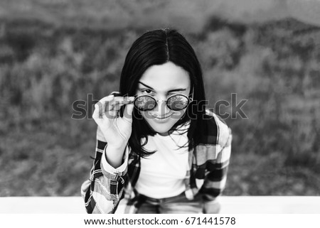 Pretty brunette girl sitting on the wooden fence outdoor in the park, black and white #671441578