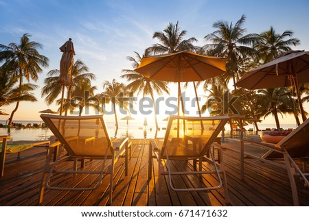 two deckchairs near swimming pool at sunset in luxury beach hotel on tropical island #671471632