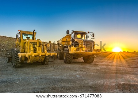 Excavator and trucks working on the excavation works of a road, moving rock and earth #671477083